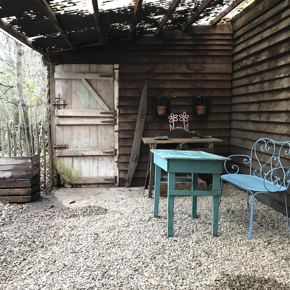 Witte Huisje Blauwe tafel onder overdekt terras