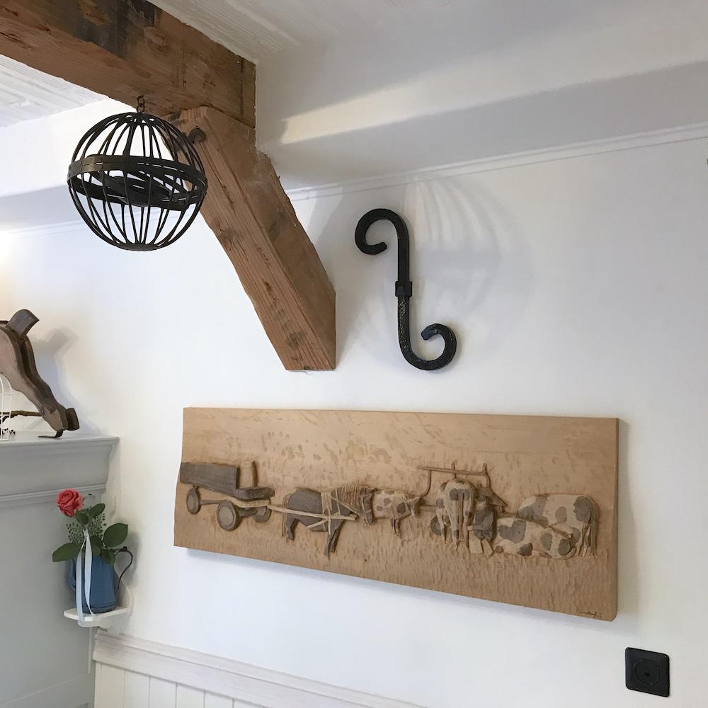 Witte Huisje tstormkandelaar en kunstwerk van hout boven de bank